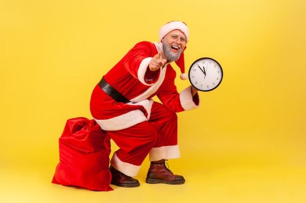 Père noël assis sur un sac rouge avec des cadeaux, tenant une horloge murale dans les mains et pointant vers la caméra.