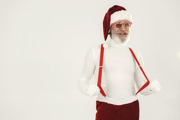 Père noël aux cheveux gris à la mode. l'homme porte des vêtements tricotés. grand-père dans un chapeau de père noël.
