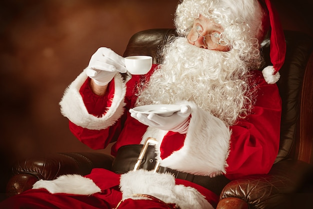 Père noël avec une barbe blanche luxueuse, un chapeau du père noël et un costume rouge assis sur une chaise avec une tasse de café