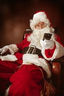 Père noël avec une barbe blanche luxueuse, un chapeau de père noël et un costume rouge assis sur une chaise avec télécommande tv