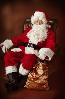 Père noël avec une barbe blanche luxueuse, un chapeau de père noël et un costume rouge