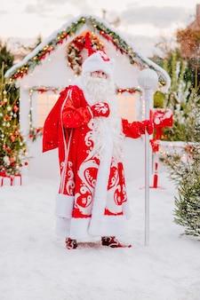Père noël avec un bâton pose dans la neige