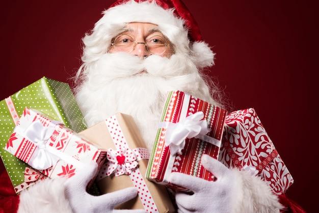Père noël avec beaucoup de coffrets cadeaux