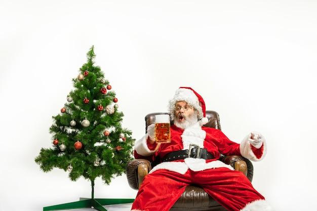 Le père noël buvant de la bière près de l'arbre de noël félicitant a l'air ivre et heureux