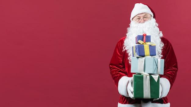 Père noël avec des cadeaux colorés dans les mains