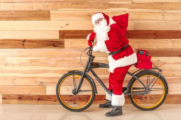 Père noël avec des cadeaux de noël et vélo près du mur en bois
