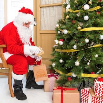 Père noël sur une chaise mettant des cadeaux sous un arbre