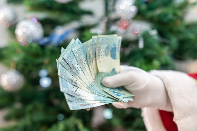 Père noël comptant des billets de banque brésiliens