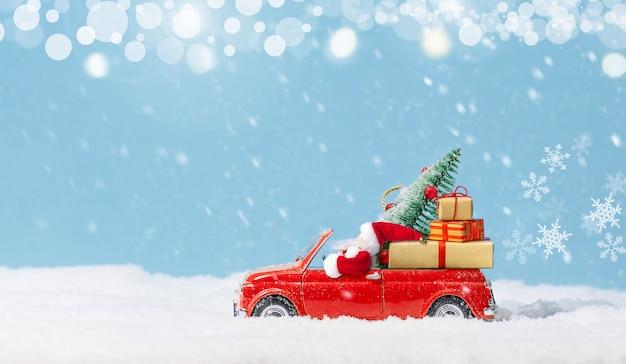 Père noël conduisant une petite voiture rouge, transportant un arbre de noël et des cadeaux sur fond de neige. fond de noël. carte de vacances. espace de copie.