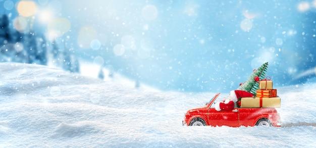 Le père noël conduit la voiture jouet rouge et offre des cadeaux et un arbre de noël sur fond neigeux. fond de noël ou du nouvel an. carte de vacances. espace de copie.