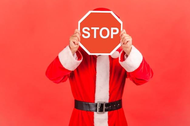 Père noël couvrant le visage avec stop , personne anonyme tenant un panneau de signalisation rouge, avertissement