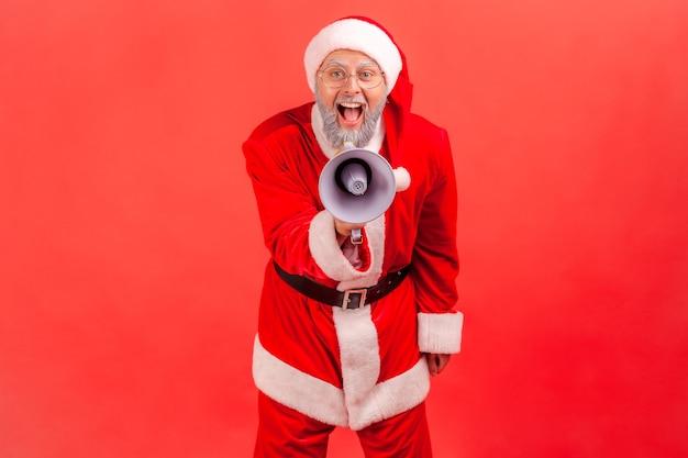 Le père noël crie fort avec un mégaphone dans les mains, regarde la caméra, proteste.