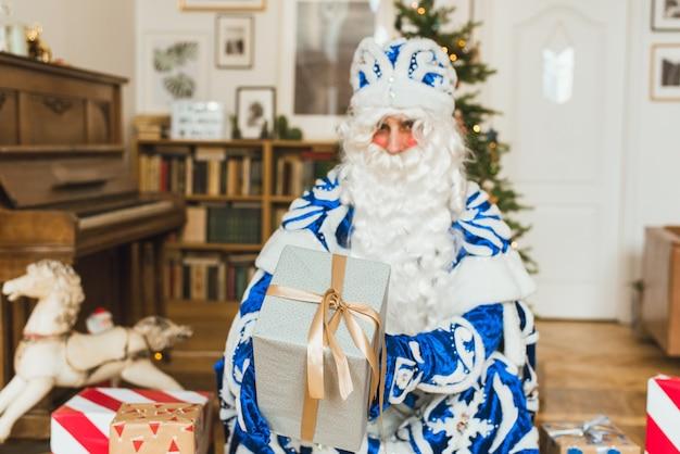 Le père noël dans un manteau de fourrure bleu sur fond de guirlande donne un cadeau à la caméra.