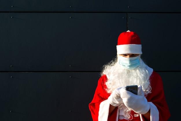 Père Noël Dans Un Masque Médical Avec Un Smartphone. Salutations En Ligne, Services De Commande Pour Noël Et Nouvel An. La Distance Sociale Dans L'épidémie De Coronavirus, Une Nouvelle Réalité. Copier L'espace Photo Premium