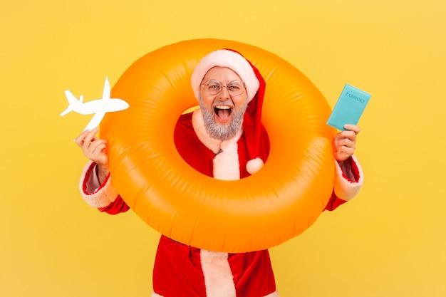 Père noël debout avec un anneau en caoutchouc sur le cou, tenant un avion en papier et un passeport dans les mains