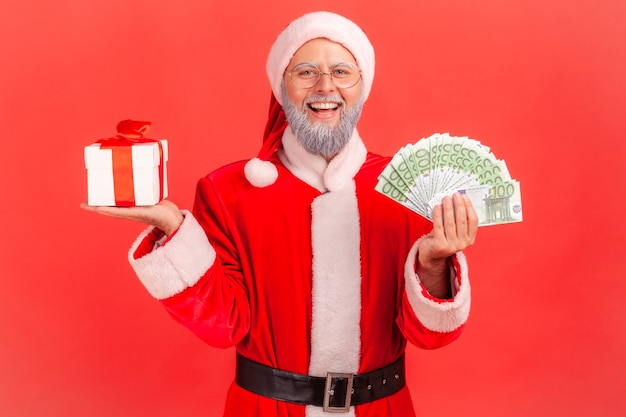 Père noël debout avec boîte de cadeau de noël et grosse somme d'argent en mains.
