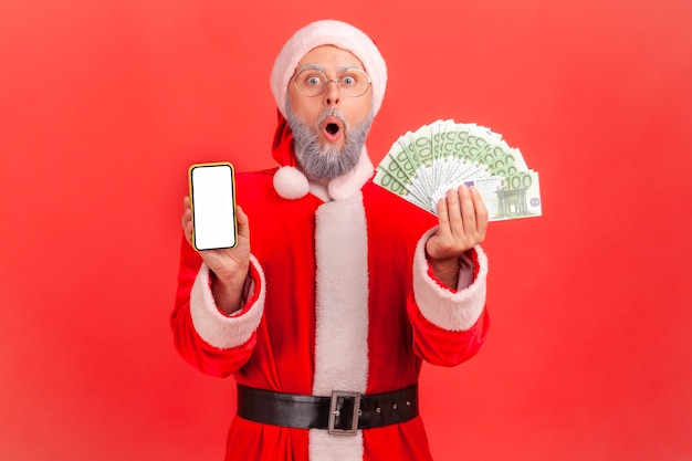 Père noël debout avec la bouche ouverte, montrant des billets en euros et un téléphone portable avec écran vide.
