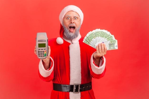 Père noël debout avec la bouche ouverte, tenant le terminal et les billets en euros dans les mains.