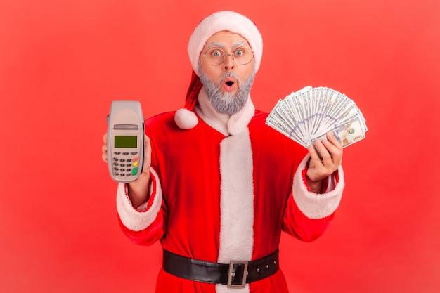 Père noël debout avec la bouche ouverte, tenant un terminal et un éventail de billets en dollars.