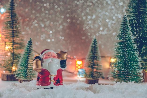 Père noël debout dans un tas de neige dans la nuit silencieuse avec arbre de noël et ornement