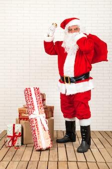 Père noël debout près des cadeaux avec cloche
