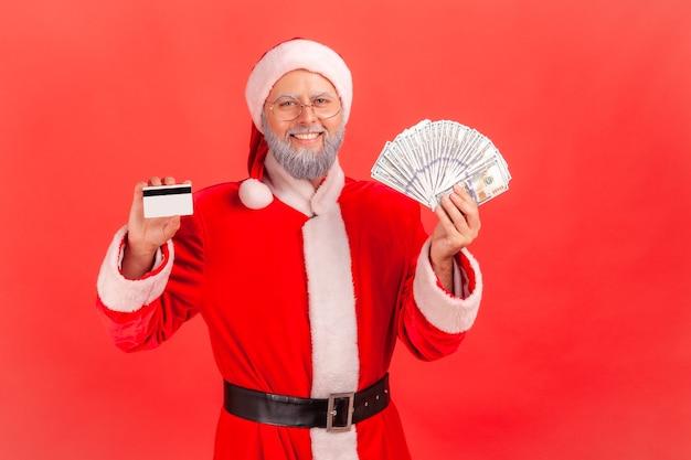 Père noël debout tenant un ventilateur de dollars et montrant une carte de crédit, un remboursement.