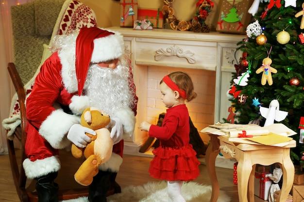 Père noël donnant cadeau à petite fille mignonne près de cheminée et arbre de noël à la maison