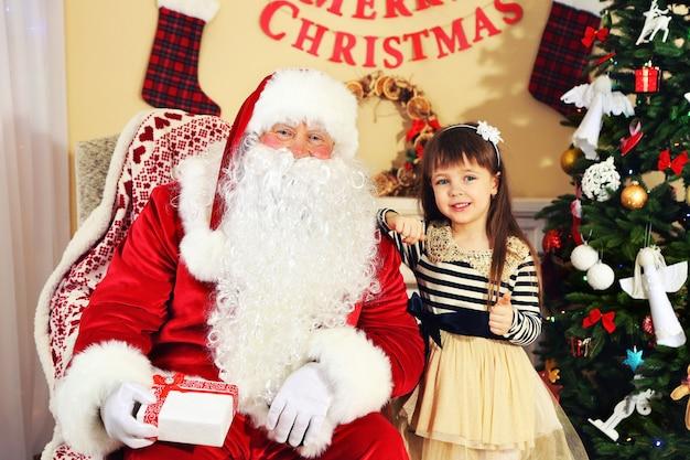 Le père noël donne un cadeau à une petite fille mignonne près de l'arbre de noël à la maison