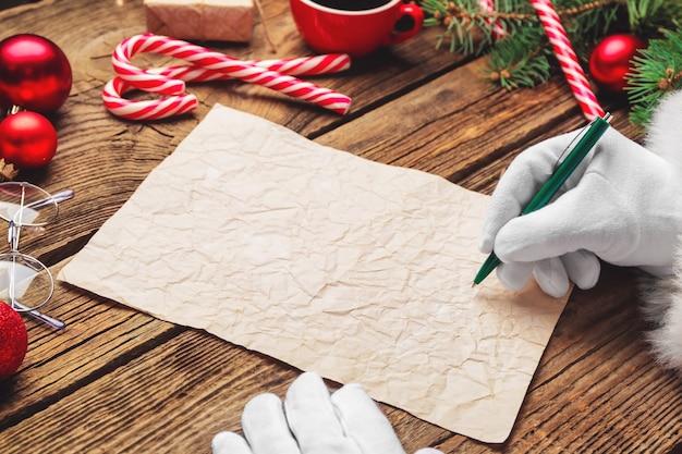 Le père noël écrit quelque chose sur une feuille de papier à table