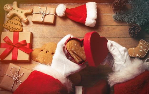 Père noël emballant des cadeaux de noël et des biscuits