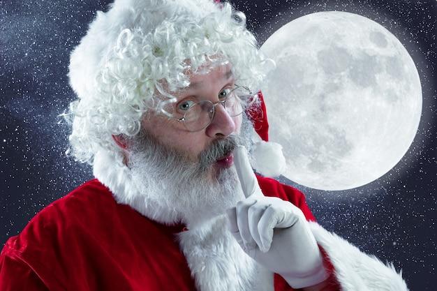 Père noël émotionnel félicitant pour le nouvel an 2020 et noël. homme en costume traditionnel chuchotant un secret avec la ville de nuit en arrière-plan. hiver, vacances, soldes, voeux. espace de copie.