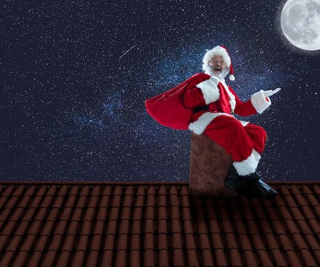 Père noël émotionnel félicitant pour le nouvel an 2020 et noël. homme en costume traditionnel grimpant sur le toit de la maison avec la ville de nuit en arrière-plan. hiver, vacances, soldes, voeux. espace de copie.