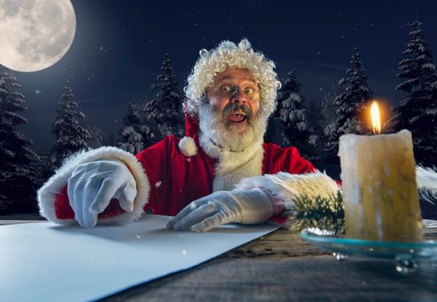 Père noël émotionnel félicitant pour le nouvel an 2021 et noël. homme en costume traditionnel écrivant une lettre, liste de souhaits éclairée à la bougie et forêt de nuit sur fond. vacances d'hiver.