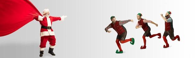 Le père noël émotionnel et ses elfes de l'entourage saluent le nouvel an 2020 et noël. l'homme en costume traditionnel et ses assistants livrent des cadeaux. hiver, ambiance vacances, cadeaux. espace de copie.
