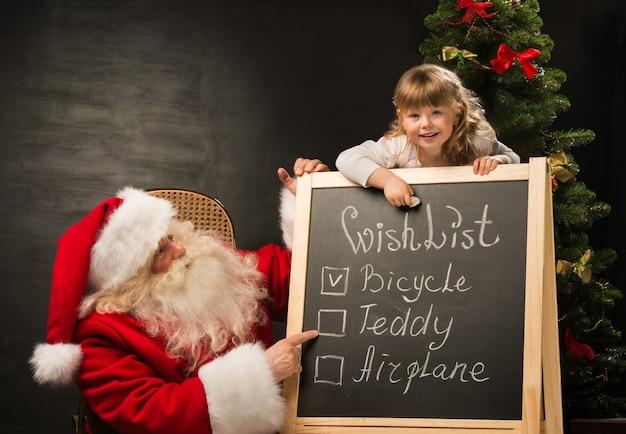 Père noël avec enfant assis près de tableau avec la liste de souhaits et en vérifiant