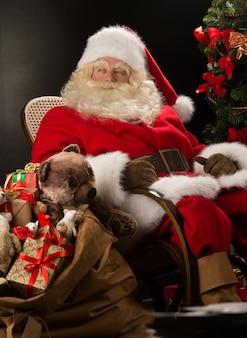 Père noël avec un énorme sac plein de cadeaux de noël