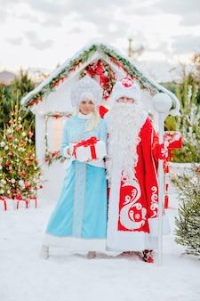 Père noël et fille des neiges avec un cadeau dans leurs mains posent dans la neige