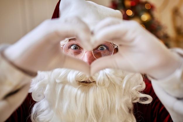 Père noël en forme de coeur avec ses doigts près de la cheminée et de l'arbre de noël avec des cadeaux. joyeux noël, concept de joyeuses fêtes