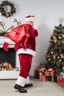 Père noël avec gros sac de cadeaux derrière le dos allant à l'arbre de noël