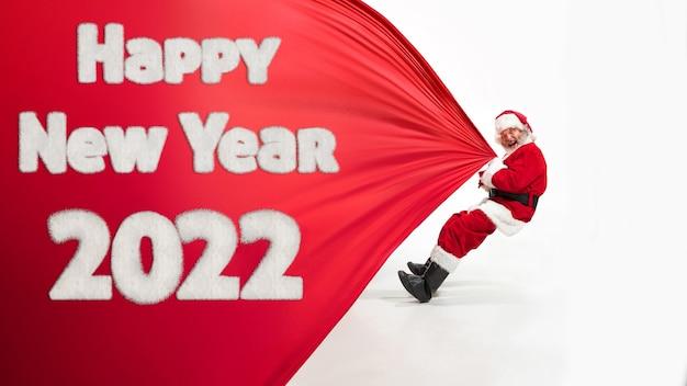Père noël isolé sur fond de studio blanc. modèle masculin de race blanche en costume traditionnel avec arbre de noël. concept du nouvel an 2020, humeur hivernale, vacances. copyspace, flyer, carte postale.