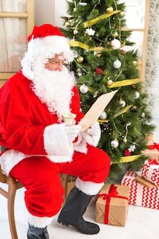 Père noël lisant un journal près d'un arbre de noël