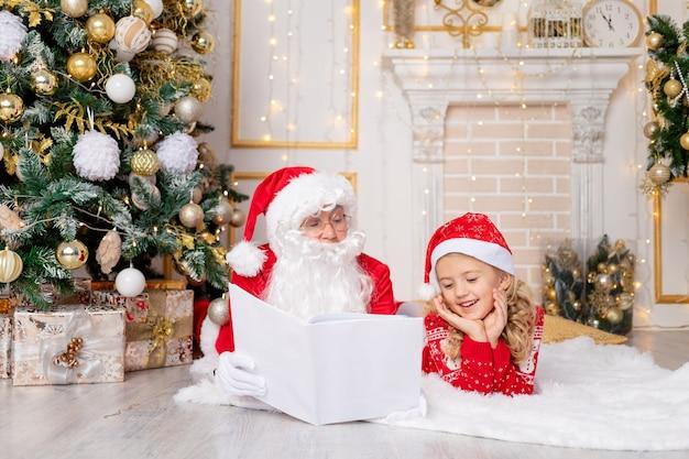 Le père noël lit un livre à une enfant fille à l'arbre de noël, le concept de nouvel an et noël