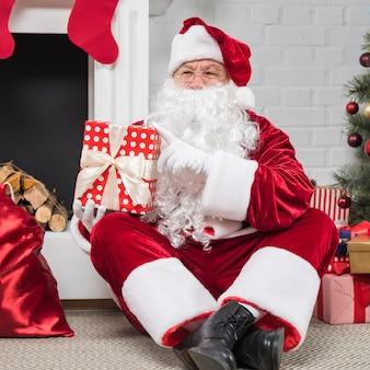Père noël à lunettes assis avec des coffrets cadeaux sur le sol