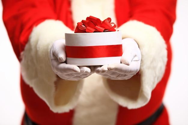 Père noël mains gantées tenant une boîte-cadeau