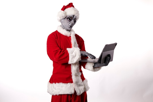 Père noël avec masque extraterrestre portant une tablette sur fond blanc