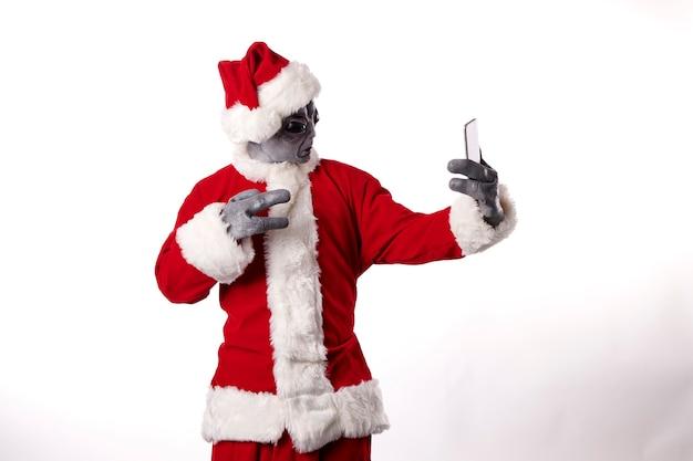 Père noël en masque extraterrestre prenant un selfie sur fond blanc