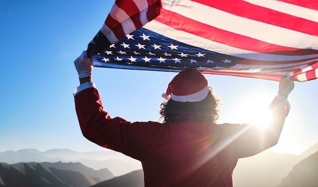 Le père noël méconnaissable brandit le drapeau américain avec des montagnes en arrière-plan