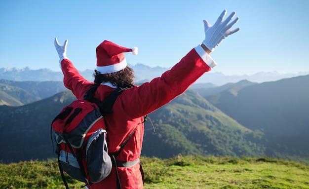 Le père noël méconnaissable avec sac à dos étend ses bras sur une montagne