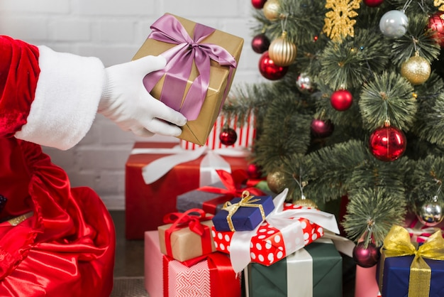 Père noël mettant des boîtes de cadeau sous l'arbre de noël