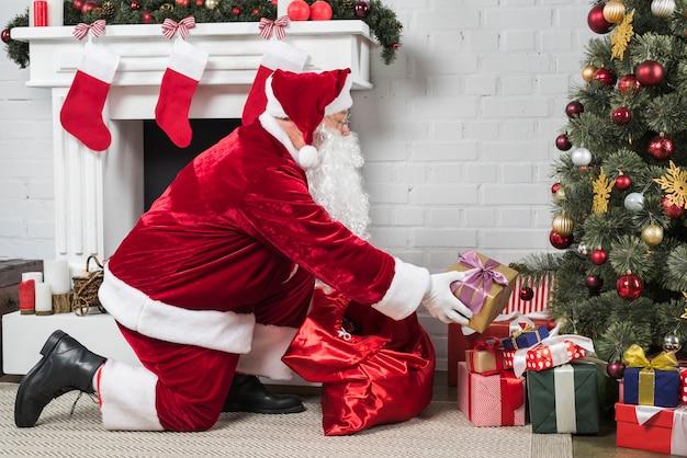 Père noël mettant des cadeaux sous un arbre de noël